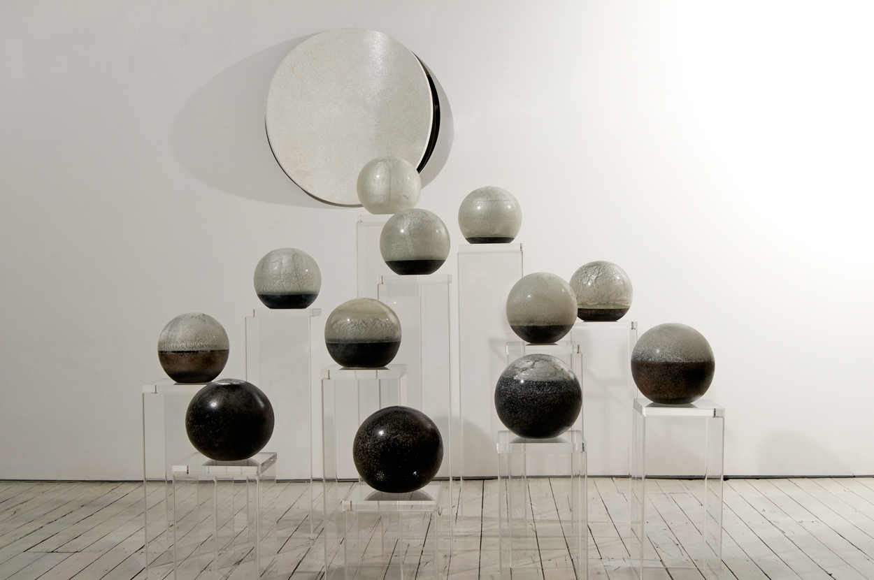 <i>Tsukimi Worlds</i>; 2010; solid glass sphere on perspex plinth; 21 cm diameter (each); in situ at studio; (background: <i>Lunar Warp 14</i>)  in collaboration with Andrew Lavery