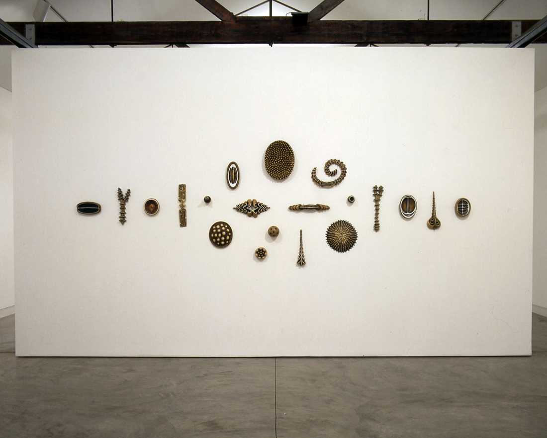 <i> Enigma Suite: Artifacts 1-20 </i>; 1997-98; bees wax, oil, resin, papier-mache; 116 x 323 x 15.5cm (overall); Exhibited at Sherman Galleries in 1998 (Tapestry of Detail exhibition)