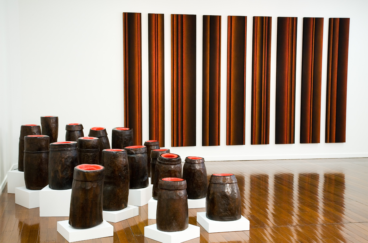 <i>Personae Suite: Nos. 1-17</i>; 2000;  Rajasthani wooden mortars, bees wax, pigment, on wooden plinths; 60 high x 30 diameter (average size)